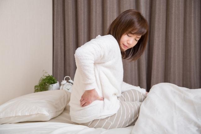 起きる時の辛い腰痛に悩む女性